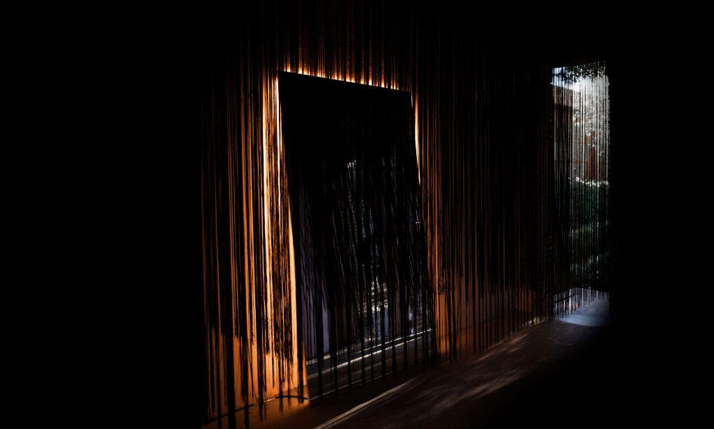 diseno_exposicion_efimera_espacio_strand_light_espejo_negro_retroiluminacion_cortina_hilos_lateral
