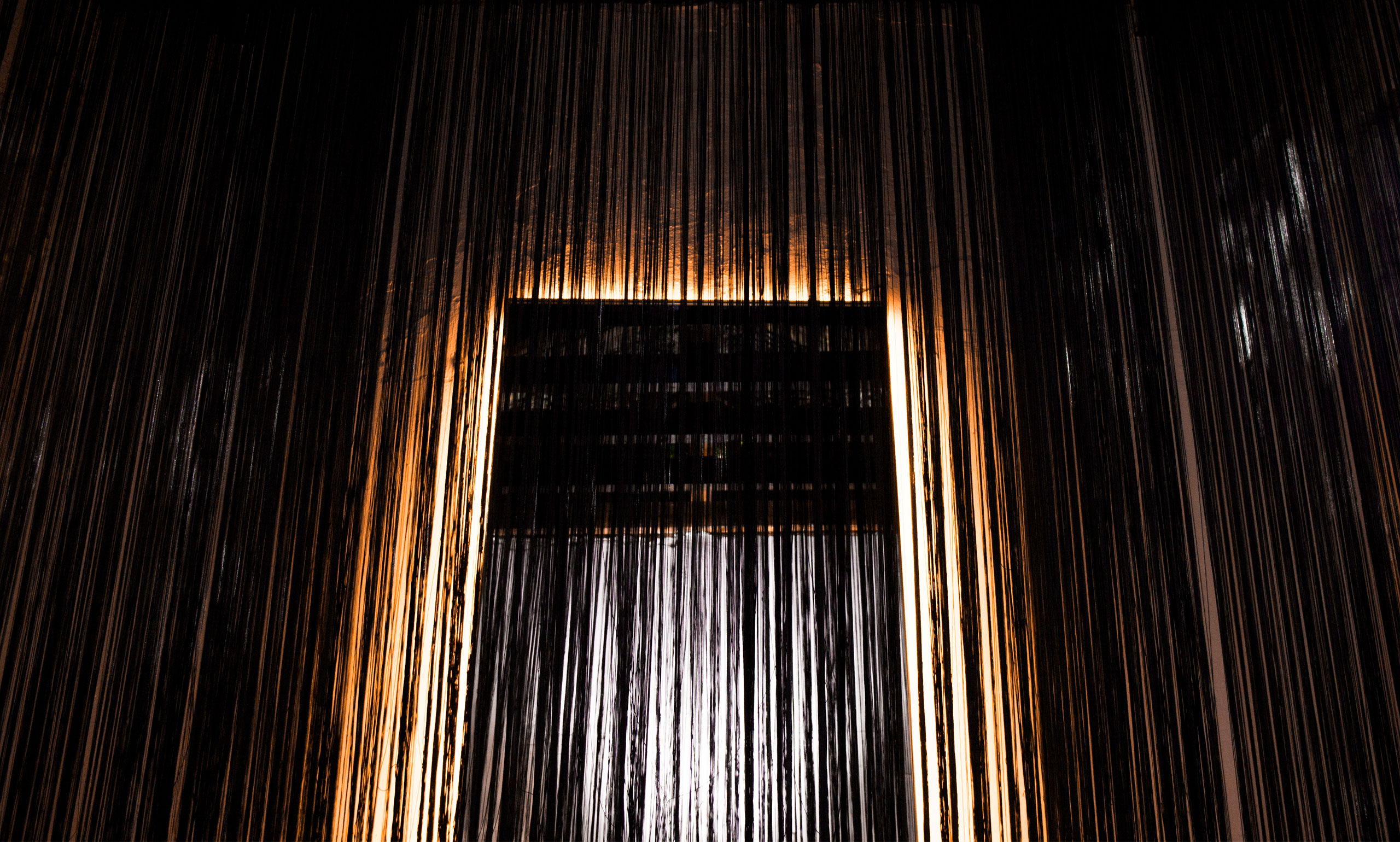diseno_exposicion_efimera_espacio_strand_light_espejo_negro_retroiluminacion_cortina_hilos_frontal
