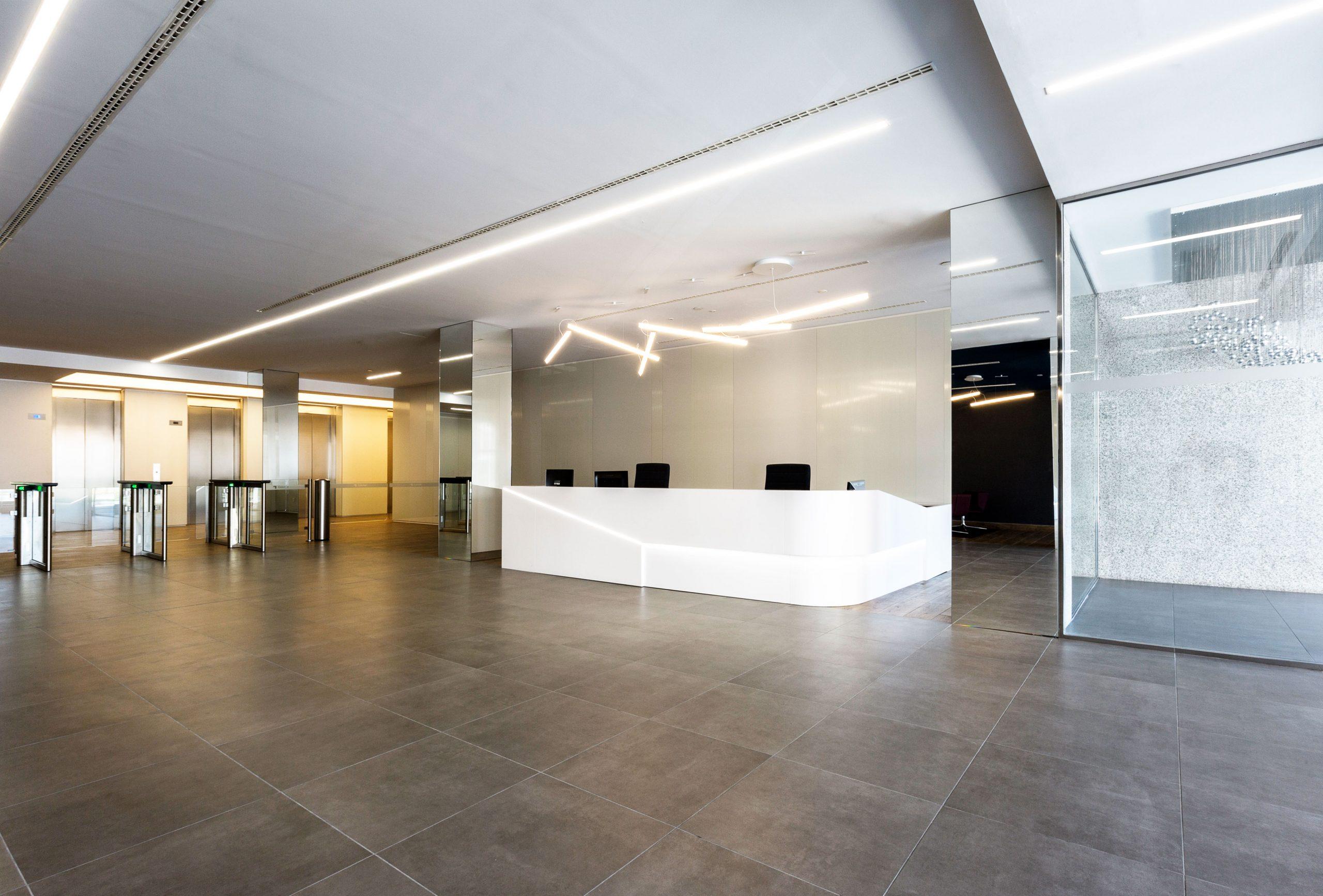 arquitectura_corporativa_mostrador_recepcion_lamparas_vibia_suelos_porcelanosa